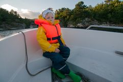 Sitting on a bow of a boat child riding back home Stock Photo
