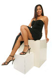 Sitting on the box. Beautiful Philippine girl kicks back on boxes in black dress isolated on white Stock Image