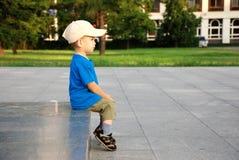 The sitting boy. The boy sitting on a granite podium Stock Image