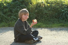 Sitting boy eating an apple. Thinking little boy eating a red apple while sitting on street Stock Photo