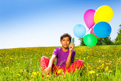 Sitting boy with flying balloons in summer Royalty Free Stock Photo
