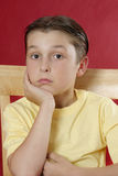Sitting boy resting head on hand Stock Images
