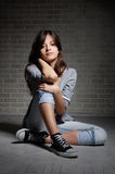 Sitting brunette girl in gym shoes. Royalty Free Stock Image
