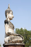 Sitting Buddha against Blue Sky. An ancient statue of Buddha with a marbling pattern from reconstruction sits on the grounds of Sukothai Historical Park in Stock Images