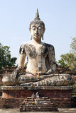 Sitting Buddha against Blue Sky. An ancient statue of Buddha with a marbling pattern from reconstruction sits on the grounds of Sukothai Historical Park in Stock Photography