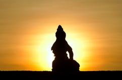 Sitting Buddha against rising sun Stock Photos
