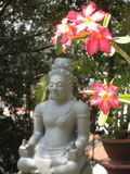 Sitting Buddha and flowers. Sitting Buddha and yellow pink flowers in the garden in Vietnam royalty free stock photo