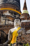 Sitting Buddha in meditation, ruins in Thailand. Ancient sculpture of a buddha in yellow robes. Temples and pagodas in Ayutthaia, ancient capital of Thai Royalty Free Stock Photos