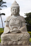 Sitting Buddha statue Hawaii outdoors green shrubs Stock Photos