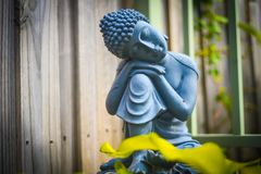 Black and white stone statue of sitting buddha in the garden royalty free stock photos