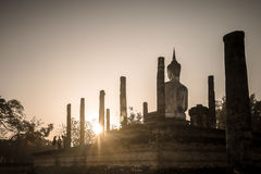 Sitting Buddha statue in a temple ruin. A big stone buddha statue is sitting in a ruin of ancient temple. The stone buddha is peacefully facing the sun rising up Royalty Free Stock Image
