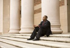 Sitting Business Man. African american business man sitting on steps infront of large pillars Royalty Free Stock Image