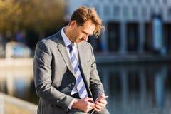 Sitting businessman handles his cellphone stock photo