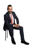 Sitting businessman smiling. An attractive and smiling businessman wearing a blue suit and red tie, sitting down on a chair with hand on his knee. White Royalty Free Stock Images