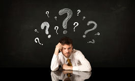 Sitting businessman under question marks Royalty Free Stock Image
