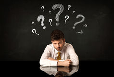 Sitting businessman under question marks Stock Photos