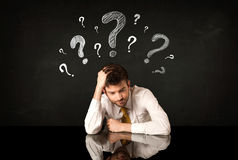 Sitting businessman under question marks Royalty Free Stock Photography