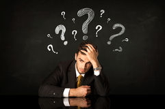 Sitting businessman under question marks Stock Images
