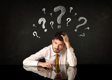 Sitting businessman under question marks Stock Photography