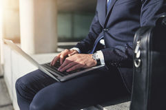 Sitting businessman working with a gray laptop Royalty Free Stock Images