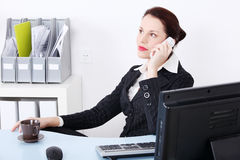 Sitting businesswoman answering the phone. Royalty Free Stock Photography