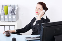 Sitting businesswoman answering the phone. Stock Images