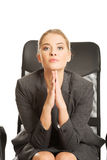 Sitting businesswoman with hands on chin Royalty Free Stock Images