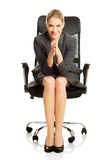 Sitting businesswoman with hands on chin Royalty Free Stock Photo