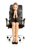Sitting businesswoman with hands on chin Royalty Free Stock Photography