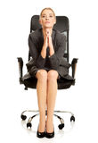 Sitting businesswoman with hands on chin Royalty Free Stock Photos