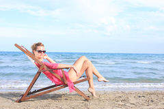 Sitting in chaise longue Stock Image