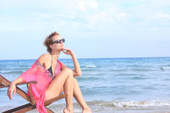 Sitting in chaise longue. Lady sitting in chaise longue on the beach stock photos