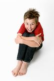 Sitting child in jeans and t-shirt Stock Images