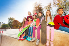 Sitting children with skateboards and helmet Royalty Free Stock Images