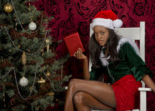 Sitting by the Christmas tree with a present for. Holding a present a beautiful young black woman sits by the tree in a big old white rocking chair in a low stock photo