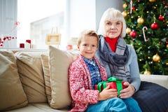 Sitting by Christmas tree Stock Photos