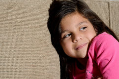 Sitting on the couch. A little girl sitting on the couch smiling Stock Images