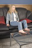 Sitting on the Couch. Beautiful blond model sitting on black leather couch Stock Photos