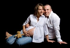 Sitting couple. Man and woman pregnant sitting on black Stock Image