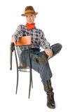 Sitting cowgirl 3. Young woman wearing cowboy clothes holding a gun Royalty Free Stock Photo