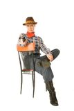 Sitting cowgirl. Young woman wearing cowboy clothes holding a gun Royalty Free Stock Photos