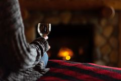 Sitting in cozy cabin by fieldstone fireplace with glass of wine. Sitting on bed in cabin with glass of wine and cozy fieldstone fireplace stock photo