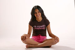 Sitting cross-legged. Teenage girl in work-out cloths sitting cross-legged stock image