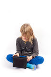 Sitting cross-legged and using a tablet Stock Photo
