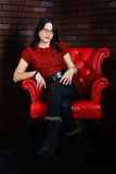 Sitting in the dark corner. Sitting in red chair in a dark corner, a beautiful young woman sits sits back in her favorite red leather chair Stock Photography