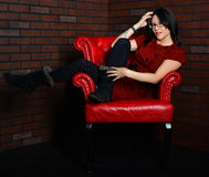 Sitting in the dark corner. Sitting in red chair in a dark corner, a beautiful young woman sits sits back with her legs up over the arm as she runs her fingers Stock Images
