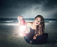 Sitting in the dark. A girl is sitting at the beach in the dark with a lantern in her hand Royalty Free Stock Image
