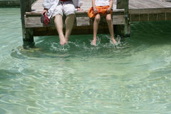 Sitting on a dock. Shot from the waist down, adult and child sitting on a wooden dock with feet in water, caucasian/white Stock Images