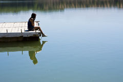Sitting in the dock. Young girl sitting in the dock of the lake Stock Photography