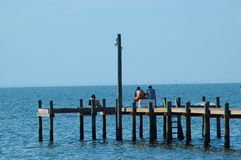 Sitting on the dock of the bay. People sitting on a dock overlooking Mobile Bay stock photos
